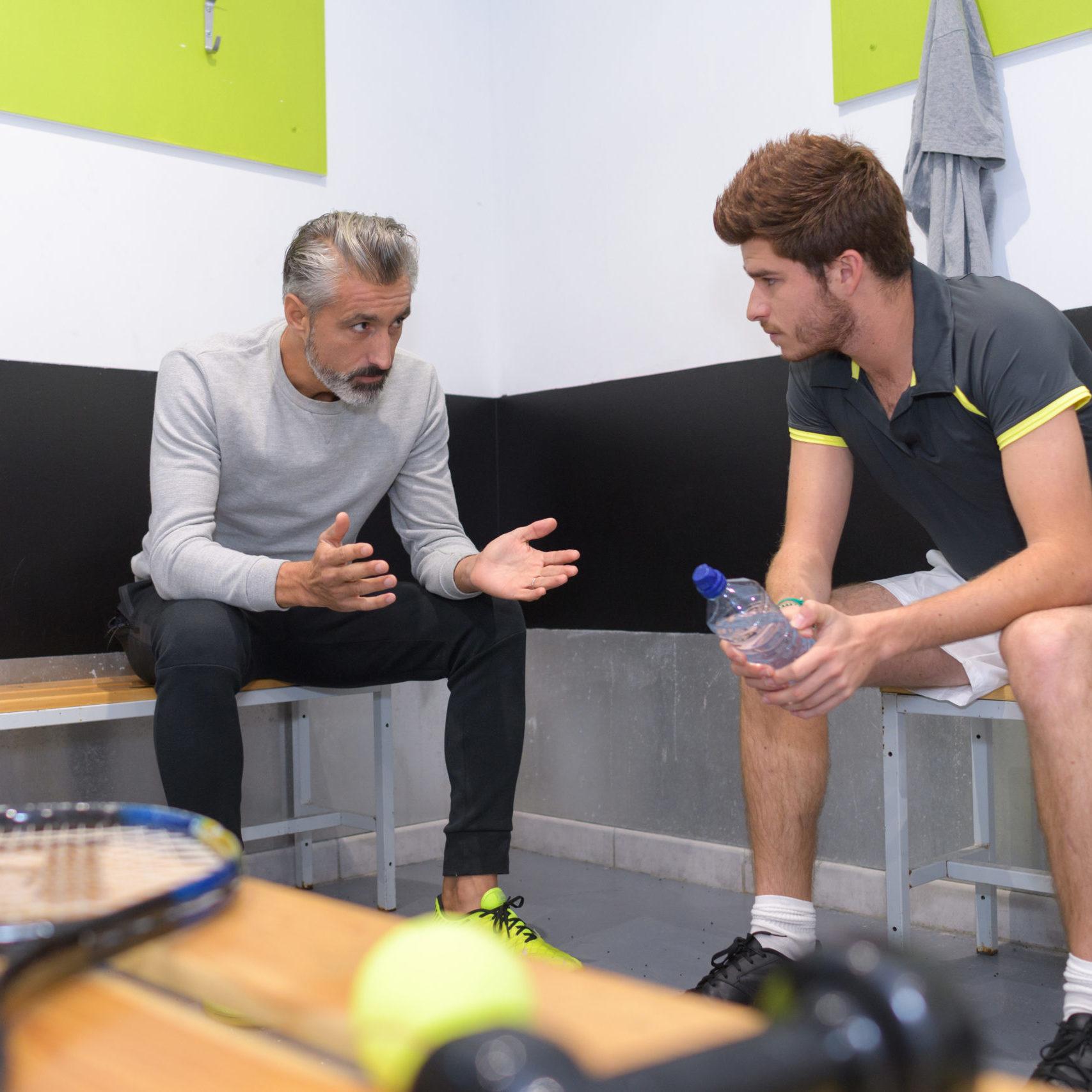 coach talking to tenis player in locker room